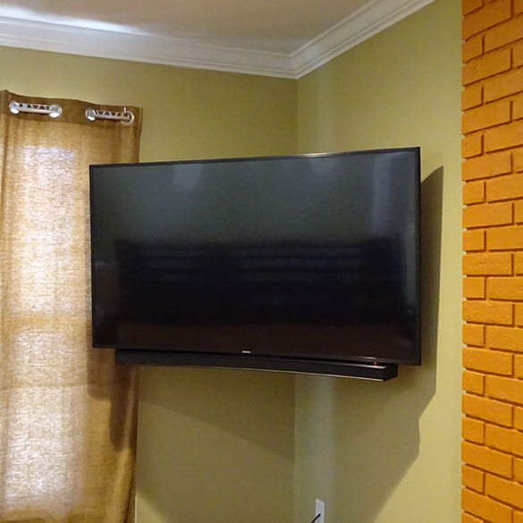 Curved TV installation with sound bar mounted below.