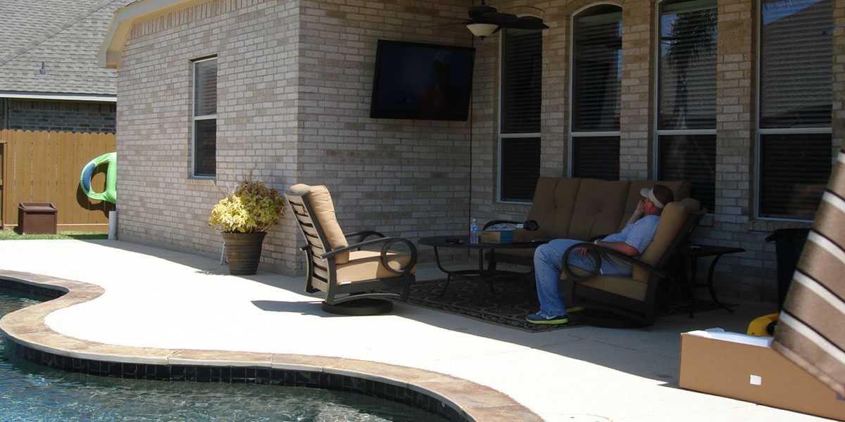 Outdoor TV install on brick wall near swimming pool.